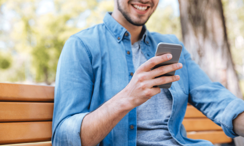 cropped-image-of-a-smiling-man-with-smartphone-sit-PHA6U4F_optimiert